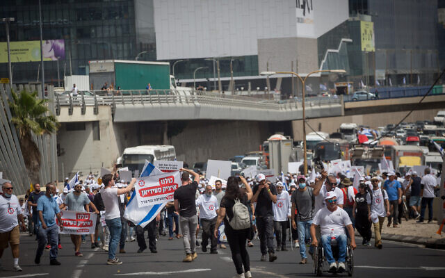 Israeli veterans and disabled IDF soldiers protest outside the Defense Ministry in Tel Aviv for improved financial and medical aid on April 18, 2021. (Miriam Alster/Flash90)