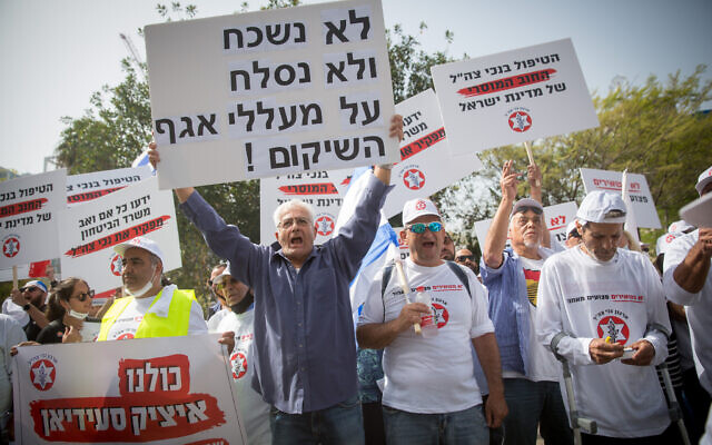 Israeli veterans and disabled IDF soldiers protest outside the Ministry of Defense in Tel Aviv for better financial and medical aid, April 18, 2021. (Miriam Alster/FLASH90)
