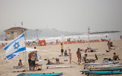 Israelis enjoy the beach in Tel Aviv on a hot spring day, April 19, 2021 (Miriam Alster/FLASH90)