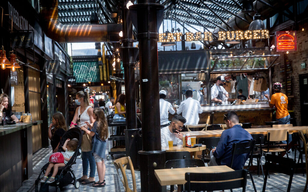 Customers enjoy dining at restaurants at the Sarona market  in Tel Aviv on April 21, 2021. (Miriam Alster/Flash90)