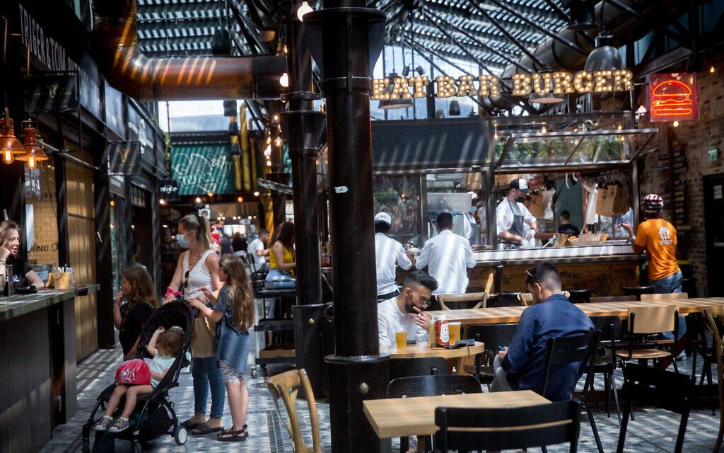 Customers enjoy dining at restaurants at the Sarona market  in Tel Aviv on April 21, 2021. (Miriam Alster/Flash90)