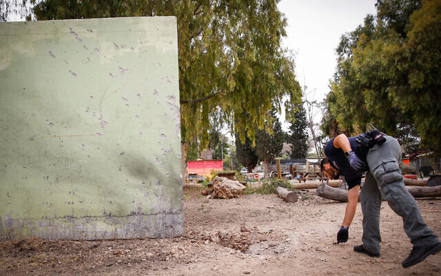 A police sapper inspects the scene where a rocket fired from the Gaza Strip fell near houses on a kibbutz in southern Israel on April 24, 2021 (Flash90)