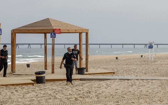 Israeli police officers walk on Zikim Beach close to the Gaza border after it was closed to visitors, on April 24, 2021 (Flash90)