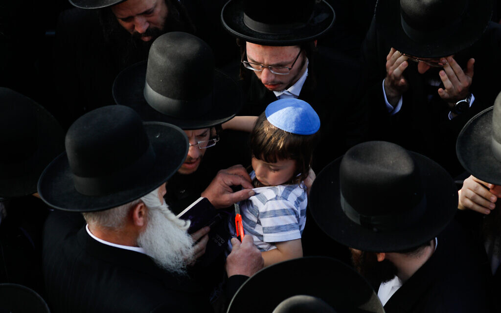 In a sign of mourning for one who lost a relative, a man cuts the shirt of the four-year-old son of Yehuda Leib Rubin who died in Meron tragedy, April 30, 2021 (Olivier Fitoussi/Flash90)