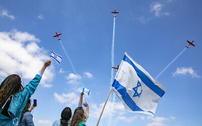 Israeli medical staff cheer an Israeli airforce aerobatic team as they fly over Shaarei Tsedek hospital in Jerusalem on Israel's 72nd Inependence Day, April 29, 2020. (Olivier Fitoussi/Flash90)