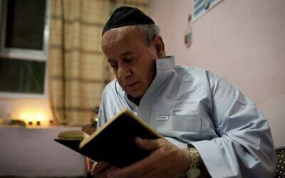 Zebulon Simantov reads a prayer book before celebrating Rosh Hashanah in Kabul, Afghanistan, September 18, 2009. (Paula Bronstein/Getty Images/File via JTA)