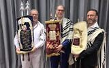 Cantor and Jewish Community of the Emirates (JCE) Co-founder Alex Peterfreund (right), Chief Rabbi of the UAE Yehuda Sarna (center) and JCE President Ross Kriel hold Torah scrolls at V Hotel Dubai, where the community's Passover services and meals were held, on April 4, 2021 (Miriam Herschlag/TOI)