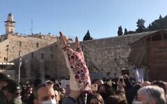 Screen capture from video of a Torah scroll brought by Labor MK Gilad Kariv to the Western Wall for use in a women's prayer group is held aloft, April, 14, 2021. (Israel Hayom)