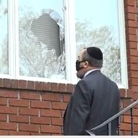 A US rabbi inspects the damage at the Chabad of Riverdale synagogue after vandals broke windows of four neighborhood synagogues on April 25, 2021. (Screen capture/News12 Connecticut)