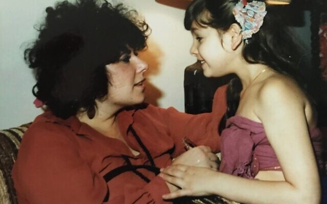 Ronit Plank with her mother in 1980, the first year after her mother returned from a year at Bhagwan Rajneesh Shree's ashram in Pune, India. Her mother wears the colors worn by the Rajneesh sannyasins (followers), and a mala (beaded necklace) with the photo of cult leader Bhagwan Shree Rajneesh. . (Courtesy)