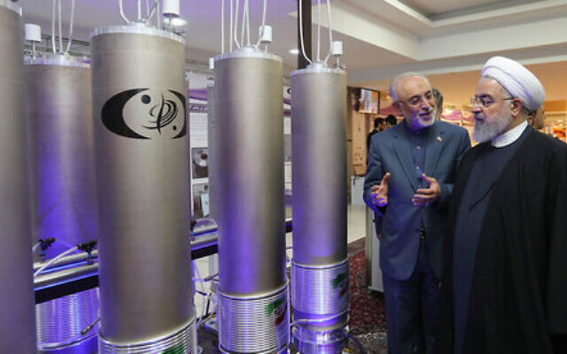 Iran's President Hassan Rouhani, right, is shown new centrifuges and listens to head of the Atomic Energy Organization of Iran Ali Akbar Salehi, while visiting an exhibition of Iran's new nuclear achievements in Tehran, Iran, April 10, 2021. (Iranian Presidency Office via AFP)