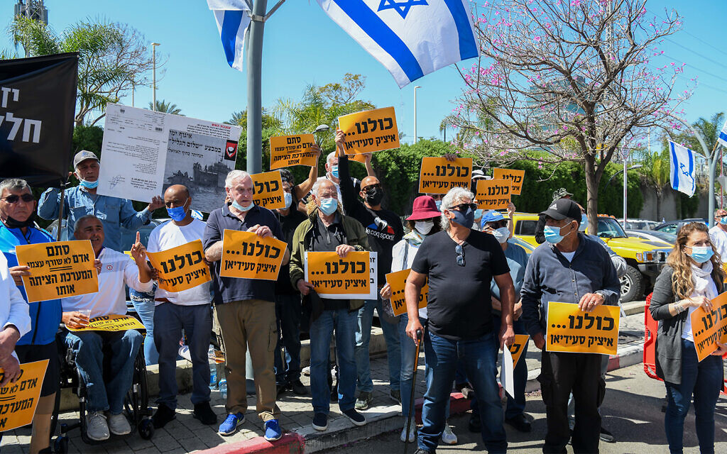 Protesters hold signs reading, 'We are all Itzik Saidyan,' outside the Defense Ministry's Rehabilitation Department in Petah Tikva, April 14, 2021. (Flash90)