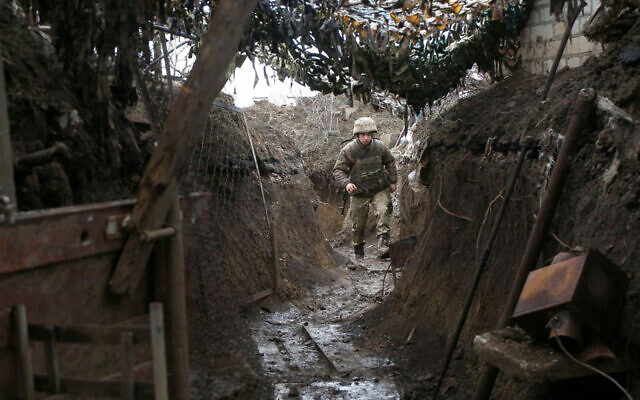 A Ukrainian serviceman walks along a trench at a position on the frontline with Russia-backed separatists near Gorlivka, Donetsk region, on April 14, 2021. (STR/AFP)