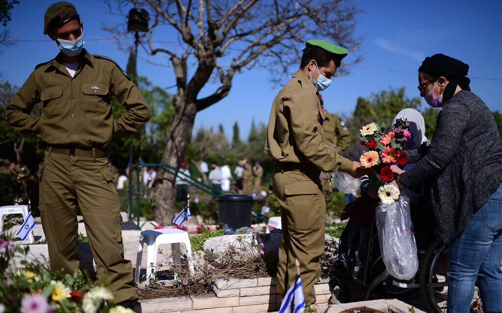 Bereaved families, friends and soldiers visit the graves of fallen troops during Memorial Day at the Kiryat Shaul Military Cemetery in Tel Aviv, April 14, 2021. (Tomer Neuberg/Flash90)