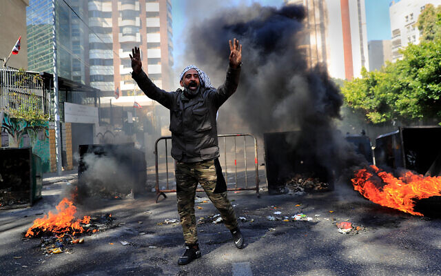 A man shouts slogans in front of burning tires and garbage containers during a protest against the increase in prices of consumer goods and the crash of the local currency, in Beirut, Lebanon, March 16, 2021. (AP Photo/Hussein Malla)