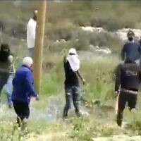 Settlers assault a Palestinian man in the West Bank in a video released on April 3, 2021. (Screenshot/Yesh Din)
