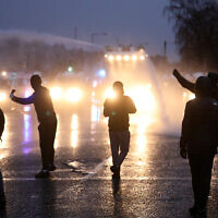 Nationalist youths gesture toward a police line blocking a road near the Peace Wall in West Belfast, Northern Ireland, April 8, 2021. (AP Photo/Peter Morrison)