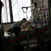 A nurse tends to a COVID-19 patient in the ICU unit at the Charles Nicolle public hospital in Normandy, France, April 15, 2021. (AP Photo/Christophe Ena)