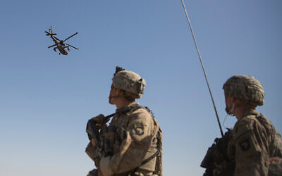 An Apache attack helicopter provides security from above while CH-47 Chinooks drop off supplies to US soldiers at Bost Airfield, Afghanistan, June 10, 2017. (US Marine Corps/Sgt. Justin T. Updegraff, Operation Resolute Support via AP)