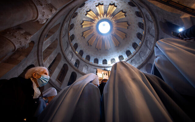 A woman wearing a face mask attends Easter Sunday Mass led by Latin Patriarch of Jerusalem Pierbattista Pizzaballa at the Church of the Holy Sepulchre in the Old City of Jerusalem, April 4, 2021. (AP Photo/Oded Balilty)
