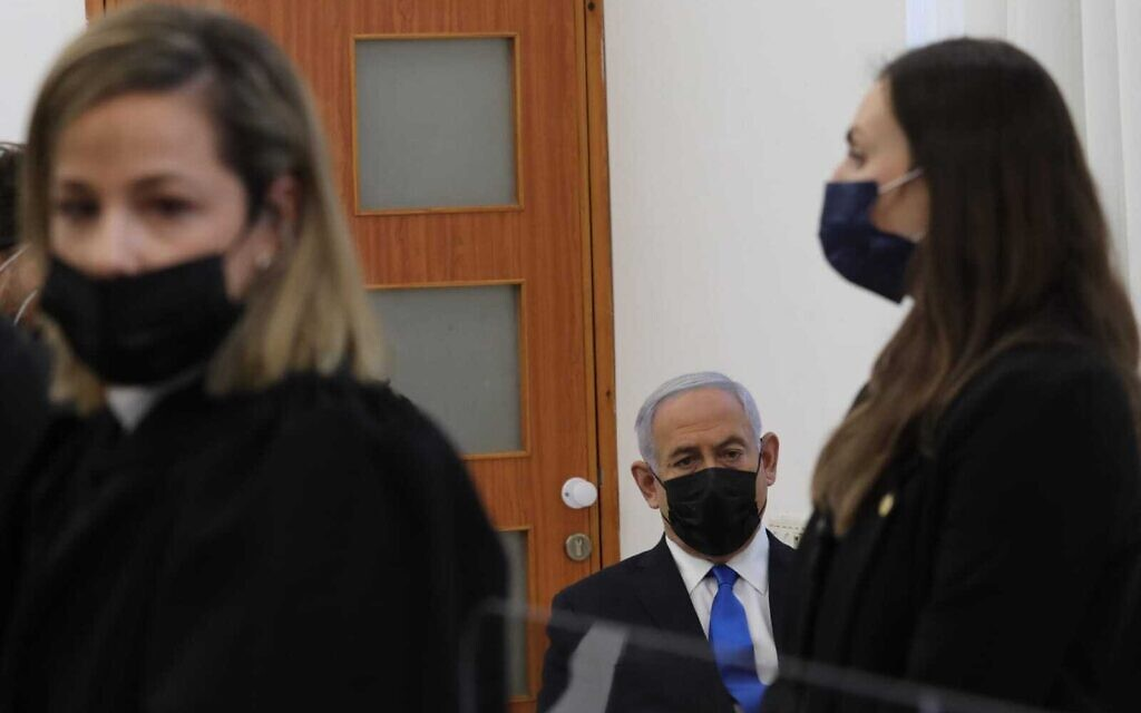 Prime Minister Benjamin Netanyahu sits alone in the back bench of the Jerusalem District Court and scribbles notes as Liat Ben Ari begins her speech, March 5, 2021. (Oren Ben Hakoon/Pool)