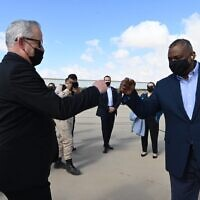 Defense Minister Benny Gantz, left, fist-bumps US Defense Secretary Lloyd Austin at the Nevatim Air Base in southern Israel on April 12, 2021. (Ariel Hermoni/Defense Ministry)
