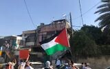 Palestinian demonstrators wave their national flag at a protest against the eviction of some Palestinians from Sheikh Jarrah in East Jerusalem on Friday, April 16, 2021 (Aaron Boxerman/The Times of Israel)