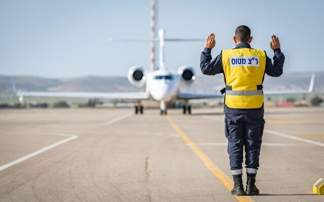 An air traffic controller directs an Oron spy aircraft down a runway at the Nevatim air base in southern Israel on April 4, 2021. (Israel Defense Forces)