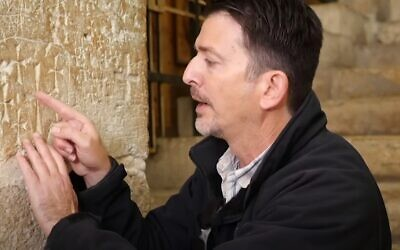 Amit Re'em of the Israel Antiquities Authority examines crosses engraved into a wall at the Church of the Holy Sepulchre in Jerusalem (video screenshot)