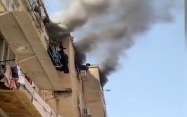 Screen capture from video of a boy, 12, leaning out of window during a fire at an apartment in Rishon Lezion, April  28, 2021. (Channel 12 News)