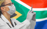 A doctor holding syringe for vaccination against COVID-19, in front of a South African flag. (Igor Vershinsky via iStock by Getty Images)