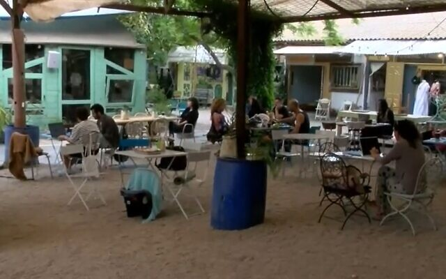 People sit outside at a cafe in the town of Pardes Hanna, April 27, 2020 (Screen grab/Walla)