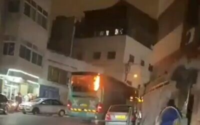 An Egged bus is seen on fire in the East Jerusalem neighborhood of Issawiya after being attacked by rioters (video screenshot)