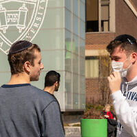 Illustrative: A Yeshiva University student wears a face mask on the grounds of the university in New York City, March 4, 2020. (David Dee Delgado/Getty Images via JTA)