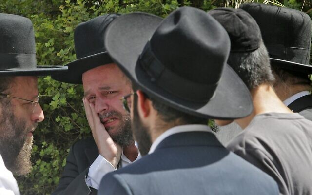 An ultra-Orthodox Jewish man weeps at a cemetery in Bnei Brak, during the funeral of one of the victims of the Meron crush on April 30, 2021. (GIL COHEN-MAGEN / AFP)