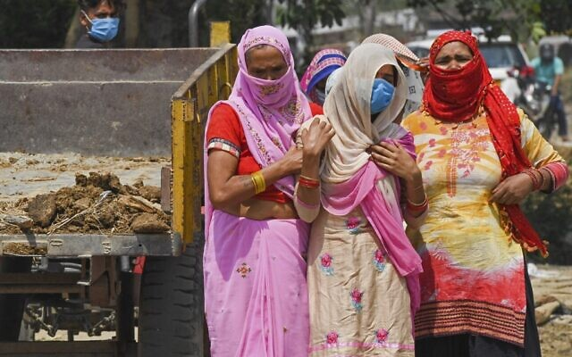 In this picture taken on May 5, 2021, relatives grieve as they arrive for the cremation of their loved one who died due to the COVID-19 coronavirus at a crematorium in Moradabad (Prakash SINGH / AFP)