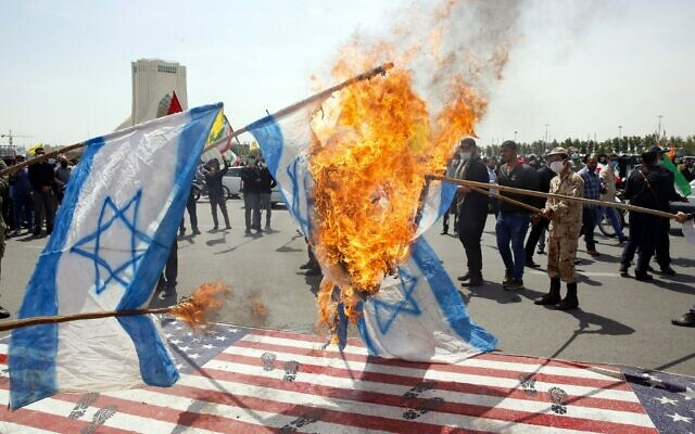 Iranians set Israeli flags on fire as they step on a US flag during a rally marking al-Quds Day at the capital Tehran's Azadi (Freedom) square, on May 7, 2021 (AFP)