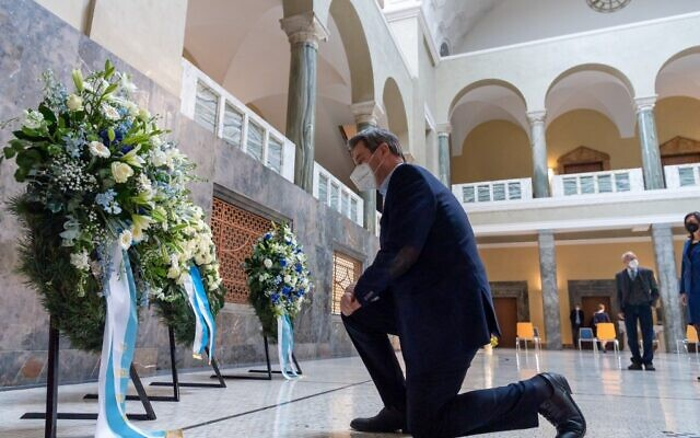 Bavaria's State Prime Minister Markus Soeder lays a wreath of flowers during a commemoration on the occasion of the 100th birthday of anti-Fascist Sophie Scholl, who was killed by the Nazi regime in 1943, in the staircase of Ludwig Maximilian University in Munich on May 7, 2021. (Peter Kneffel / POOL / AFP)