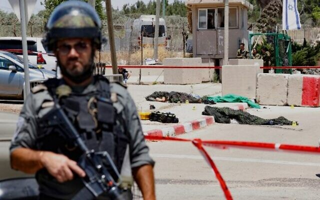 An Israeli soldier stands guard as the bodies of two Palestinian attackers, who opened fire and were killed by Israeli security forces, lie on the ground in front of the IDF military base of Salem near the West Bank town of Jenin, on May 7, 2021. (Photo by Jack GUEZ / AFP)