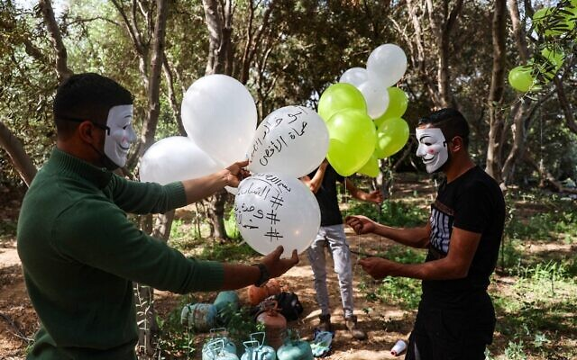 Masked Hamas members apparently prepare incendiary balloons to be launched toward Israel from the Gaza Strip, May 8, 2021. (MOHAMMED ABED / AFP)