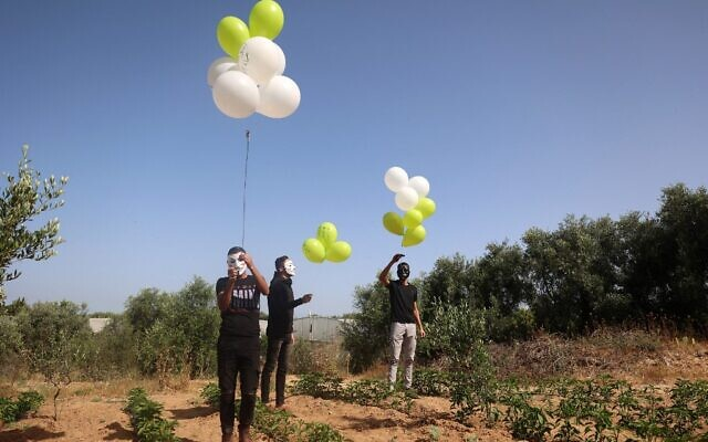 Masked Palestinians prepare to launch incendiary balloons across the northern Gaza border toward Israel, on May 8, 2021. (MOHAMMED ABED / AFP)
