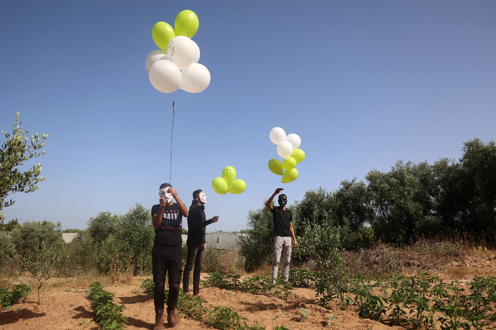 Masked Palestinians prepare to launch incendiary balloons across the northern Gaza border toward Israel