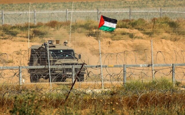 A Palestinian national flag is erected on the Israel-Gaza border, east of Khan Yunis town in the southern Gaza Strip, on May 8, 2021. (Said Khatib/AFP)
