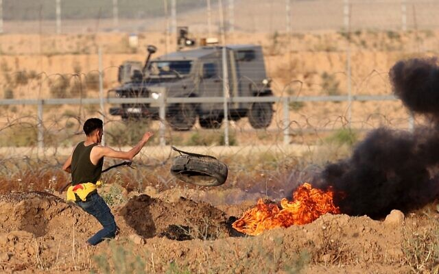 A Palestinian burns tires during a demonstration along the Israel-Gaza border, east of Khan Younis in the southern Gaza Strip on May 8, 2021 (SAID KHATIB / AFP)