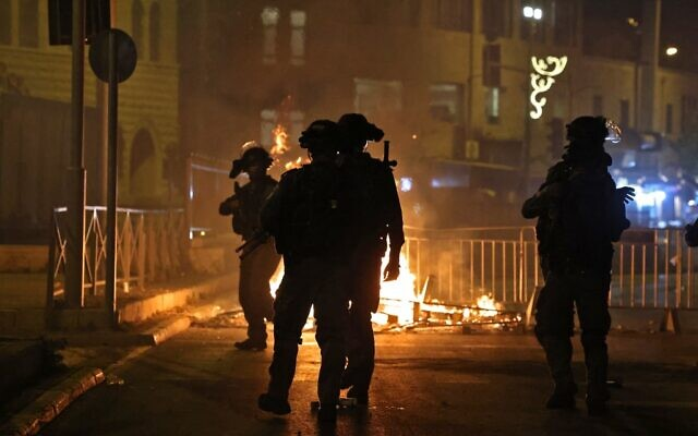 Israeli security forces stand next to a burning barricade erected in Jerusalem's Old City on May 8, 2021. (EMMANUEL DUNAND / AFP)