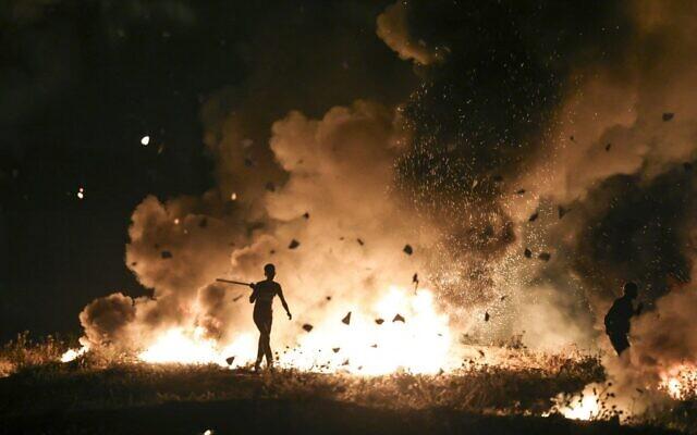 Palestinian protesters burn tires during a riot along the Israel-Gaza border, east of Gaza city on May 8, 2021. (MAHMUD HAMS / AFP)