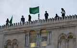 Palestinians place Hamas flags atop the Al-Aqsa mosque in Jerusalem's Old City on May 10, 2021. (Ahmad Gharabli/AFP)