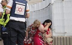Israeli rescue teams help shocked residents in a targeted residential neighbourhood in the southern city of Ashkelon on May 11, 2021, after rockets were fired by the Hamas terror group from the Gaza Strip (JACK GUEZ / AFP)