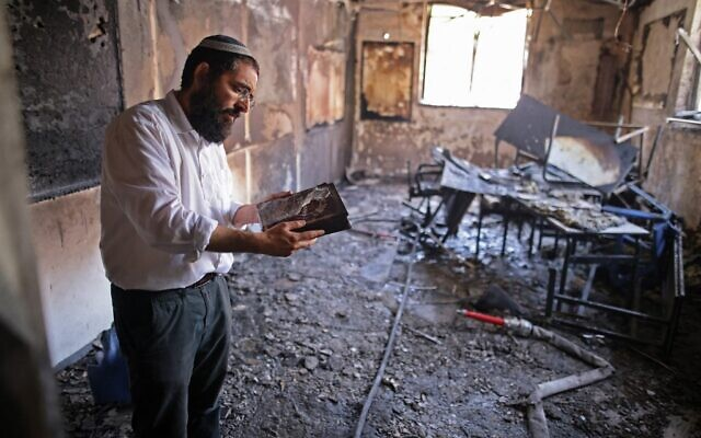 A rabbi inspects the damage inside a religious school in the central Israeli city of Lod, on May 11, 2021. The school was allegedly torched by a mob of local Arab residents on the night of May 10. (Ahmad GHARABLI / AFP)
