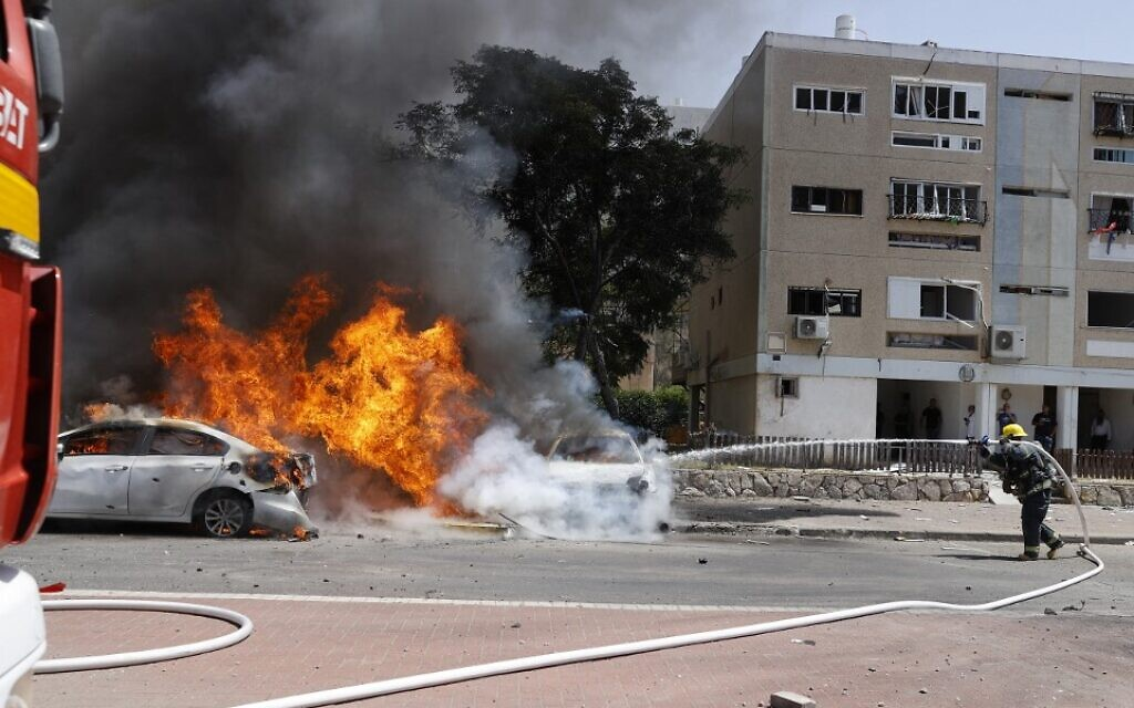 An Israeli firefighter extinguishes a burning vehicle after a rocket launched from the Hamas-run Gaza Strip hit the southern Israeli city of Ashkelon on May 11, 2021. (JACK GUEZ / AFP)